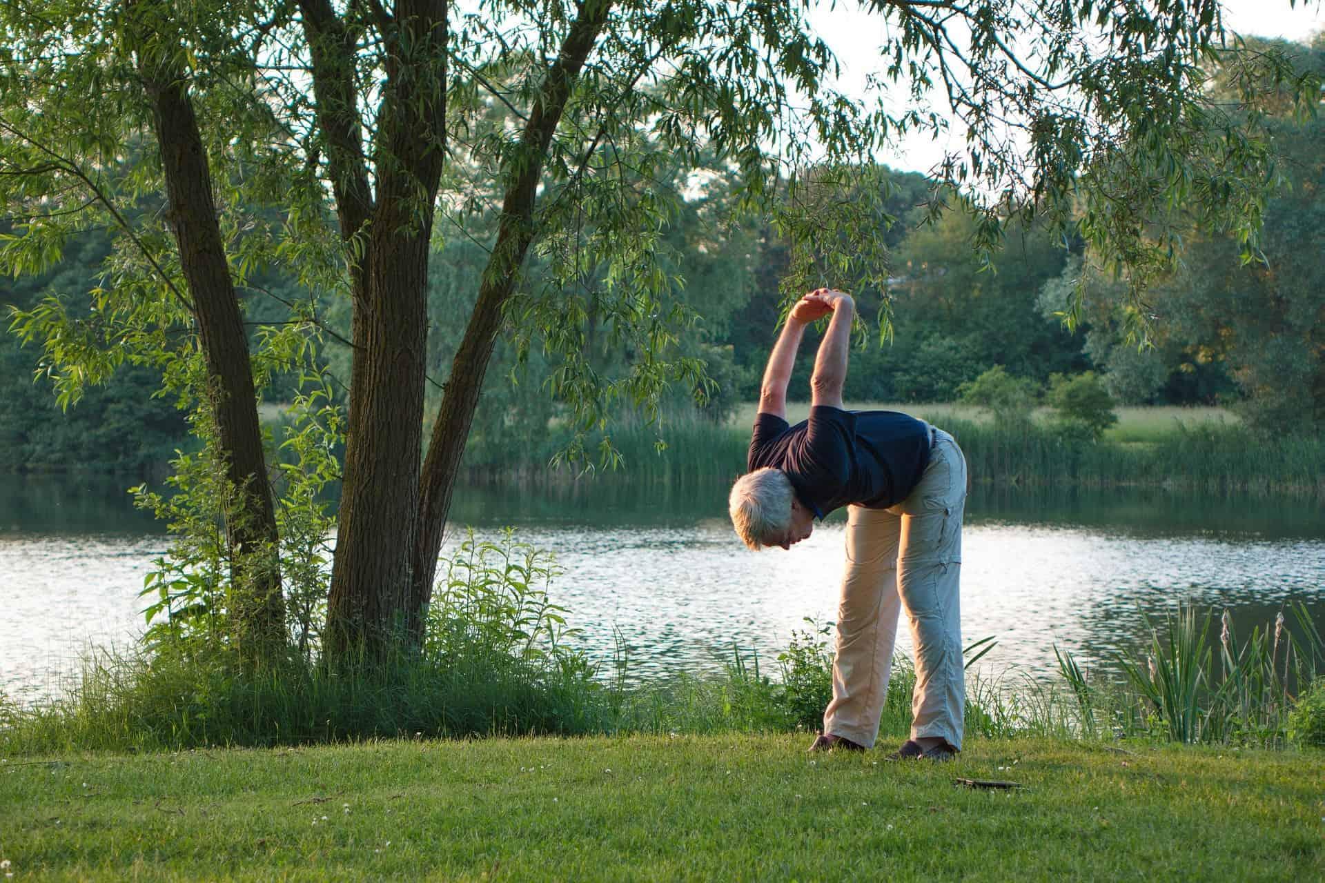 älterer Mann beim Ausdehnen nach dem Joggen an einem See