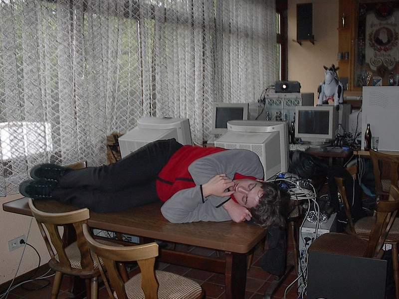 Marc schläft auf einem Tisch zwischen Computern