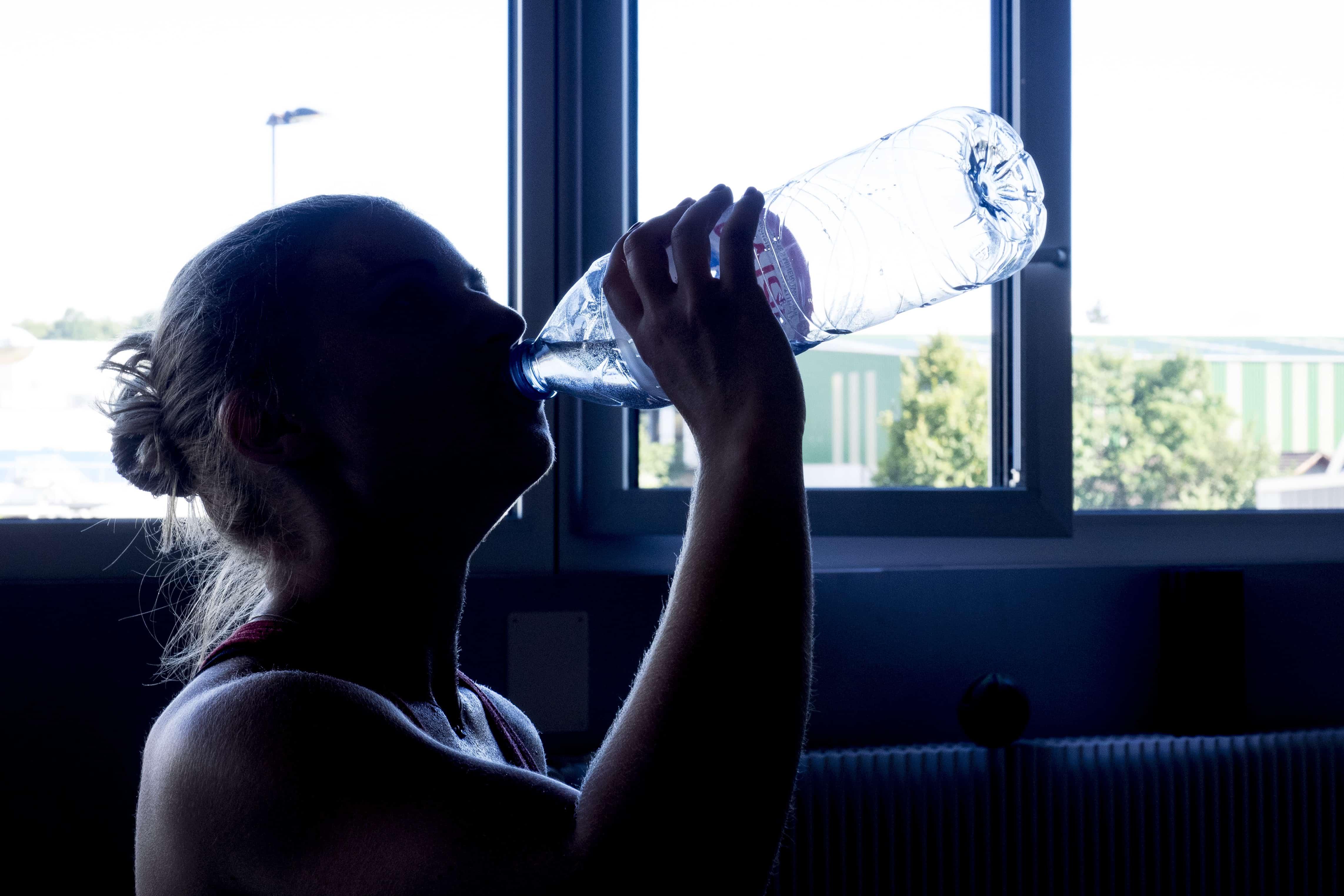 Wassertrinkende Frau mit dem richtigen Mindset zum fit werden