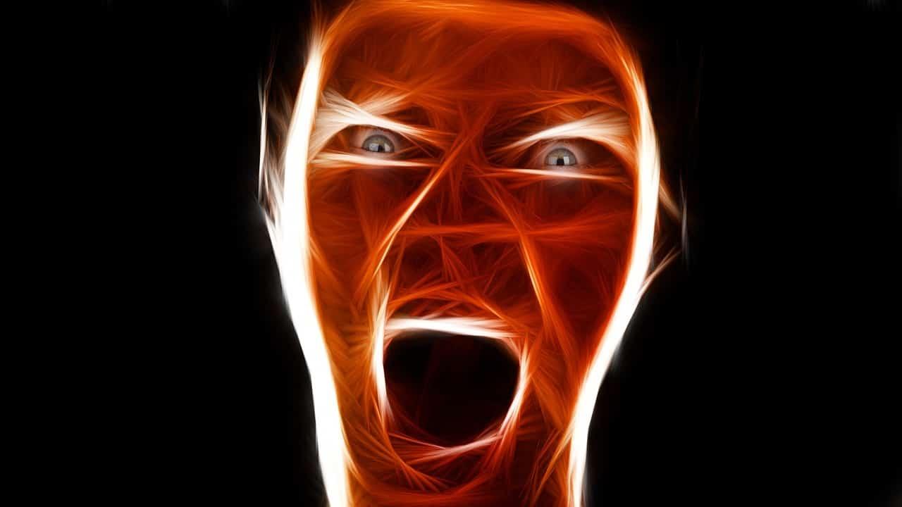 Männliches wütendes Gesicht in rot auf schwarzem Hintergrund.